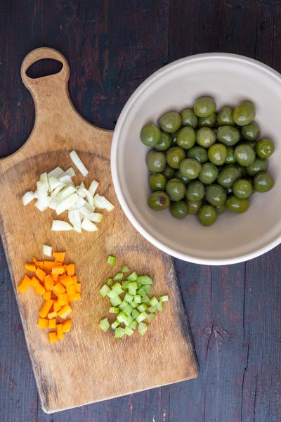 Chopped veggies & plain green olives in a grey bowl.