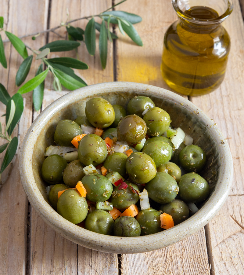 Green olive salad in a grey bowl & olive oil in a glass jar.