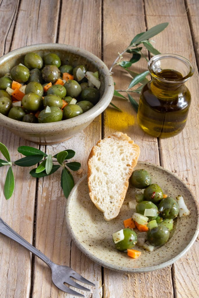 Olives in a grey bowl with some on a grey plate with a slice of bread.