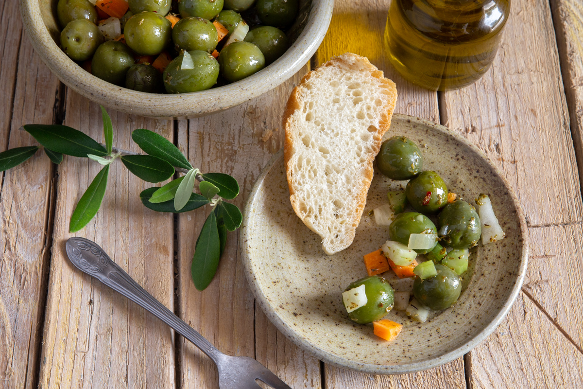 olives in a grey bowl, some olive salad & a slice of bread on a grey plate.