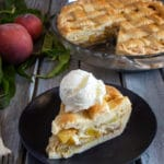 peach pie in a glass dish with a slice & a scoop of ice cream on a black plate.