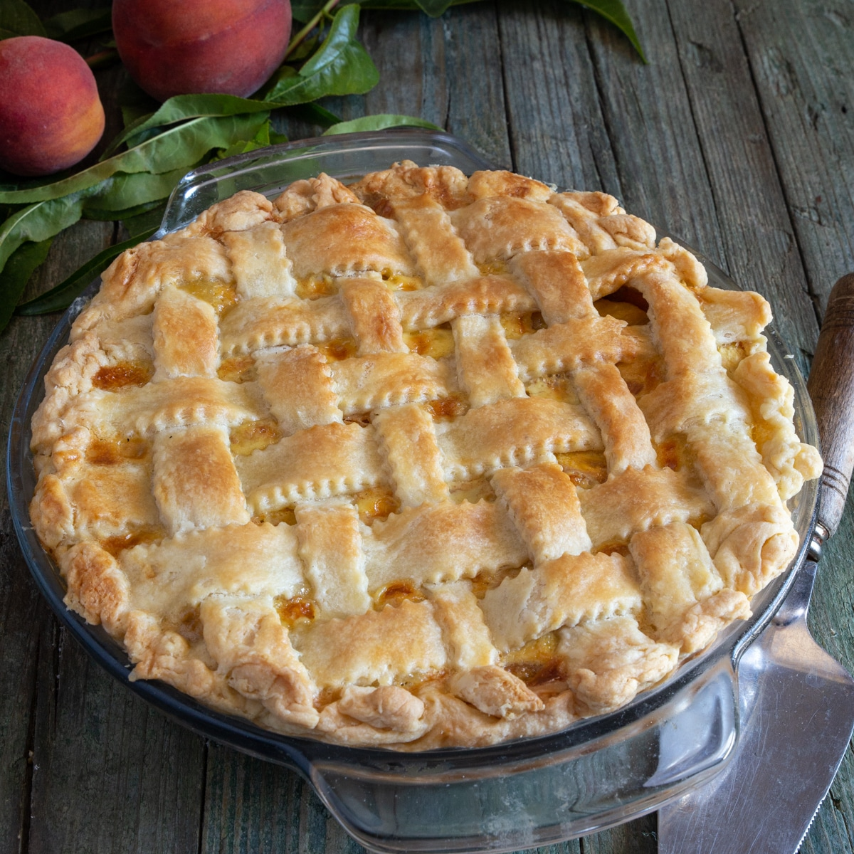 Peach pie in a glass plate, with 2 peaches and leaves on a wooden board.