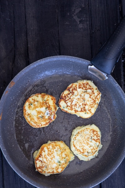4 fritters in a frying pan fried.