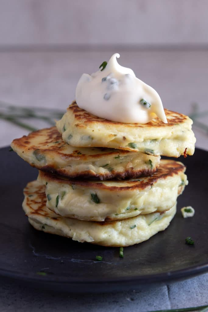 4 stacked fritters on a black plate with a dollop of chive mayo on top.