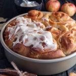 Apple cinnamon rolls in a baking pan, half frosted.