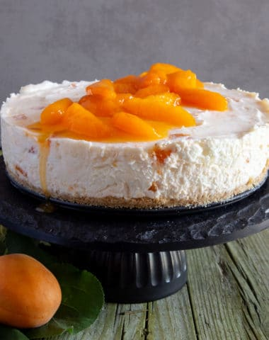 Apricot cheesecake on a black cake stand.