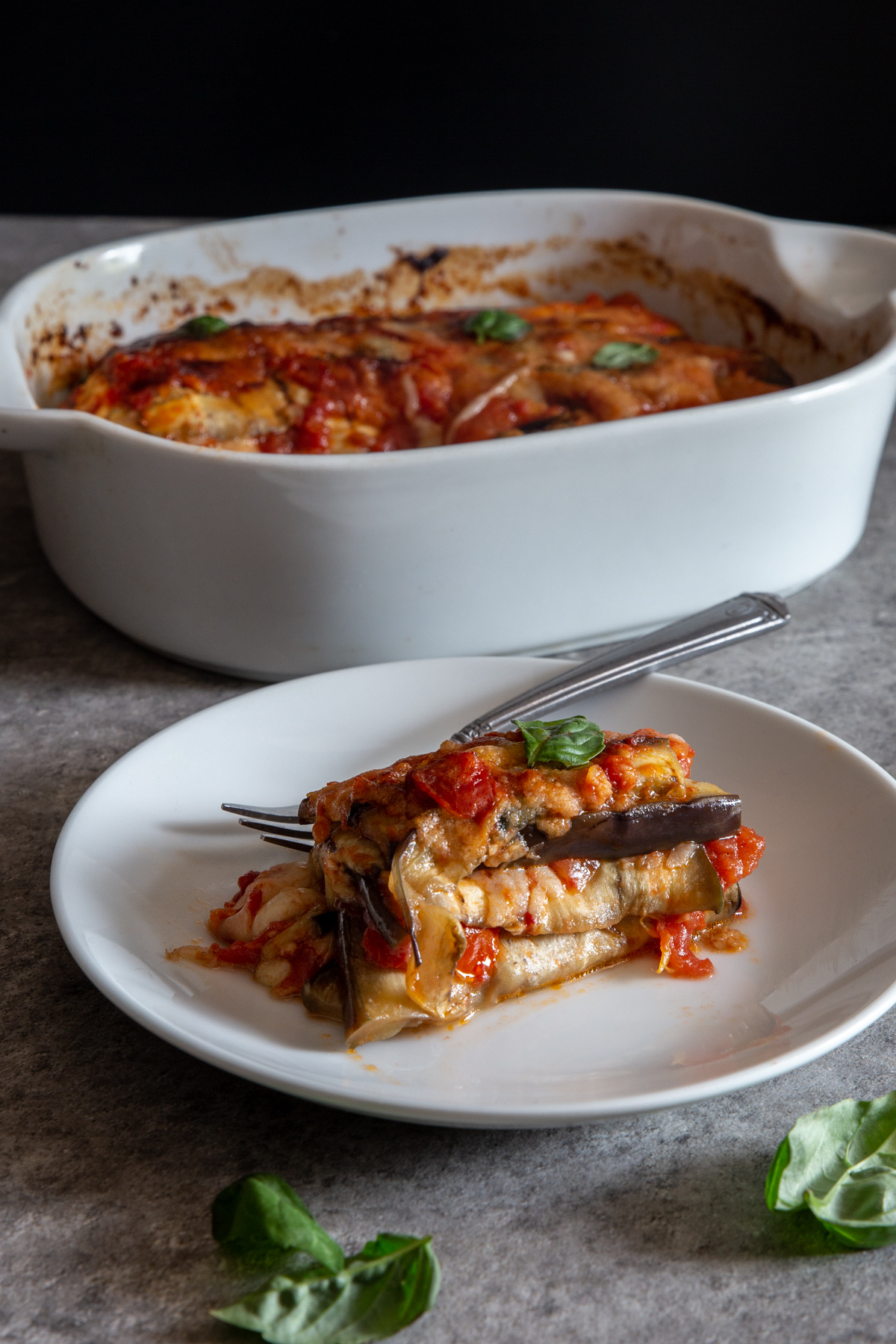 Pasticcio in a white dish with a slice on a white plate.