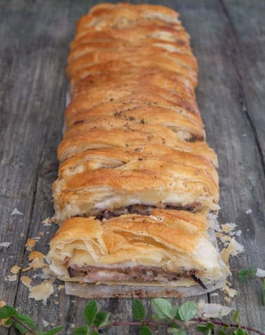 Eggplant strudel on a blue board with a slice cut.