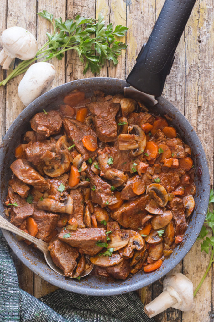 Beef mushroom stew in a frying pan with a spoon.