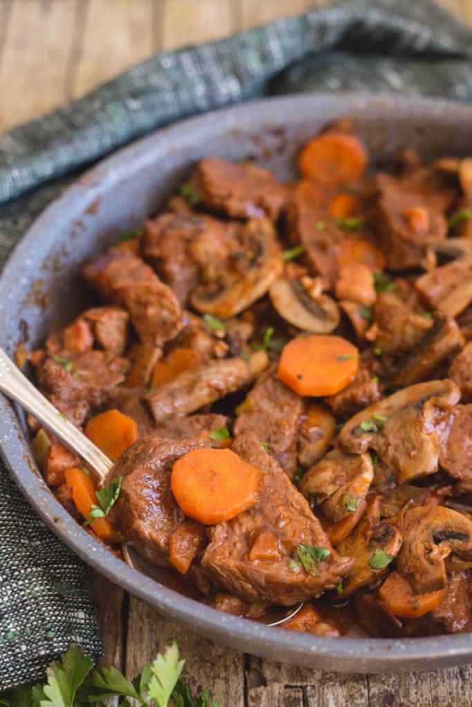 Beef stew in a black frying pan.