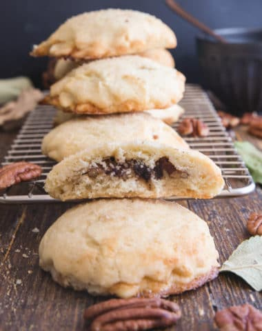 Pecan cookies on a wire rack with one cut in half.