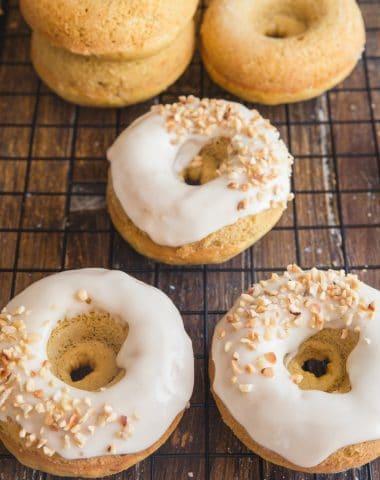 Pumpkin donuts 3 glazed, 3 plain on a wire rack