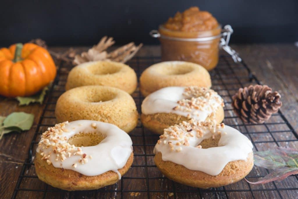 Plain & glazed pumpkin donuts on a wire rack.