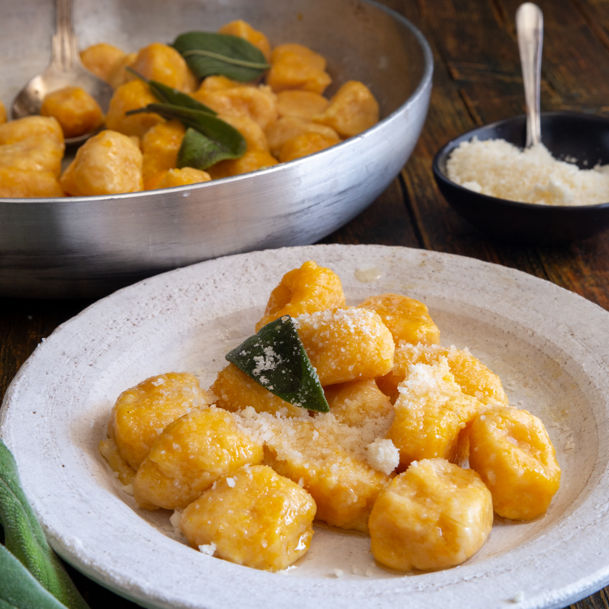 Pumpkin gnocchi in a white plate and some in a silver pan.
