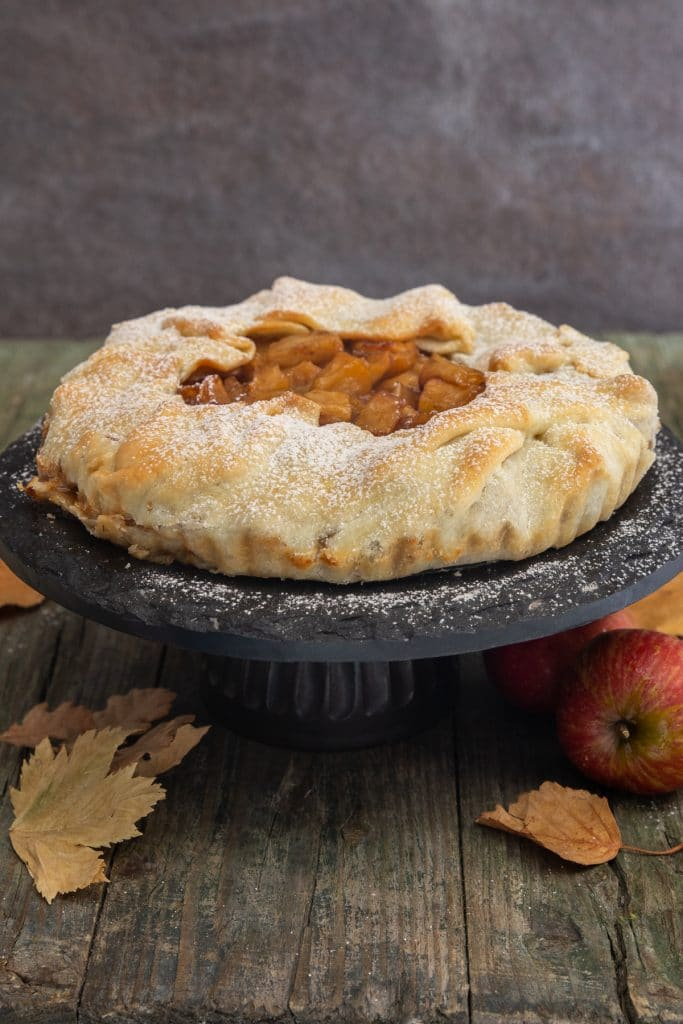 Apple galette on a black cake stand.