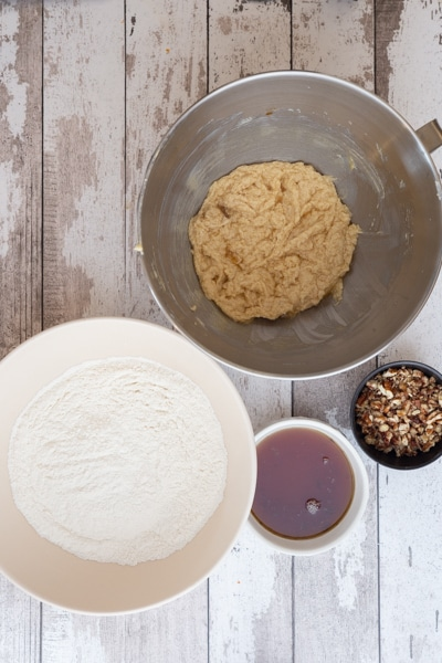 Butter & sugar creamed in mixer, whisked ingredients in white bowl & maple syrup & nuts in small bowls.
