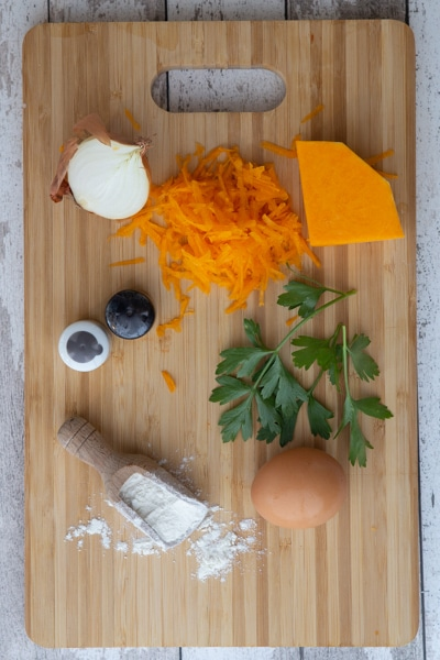 Ingredients for fritters on a wooden board.