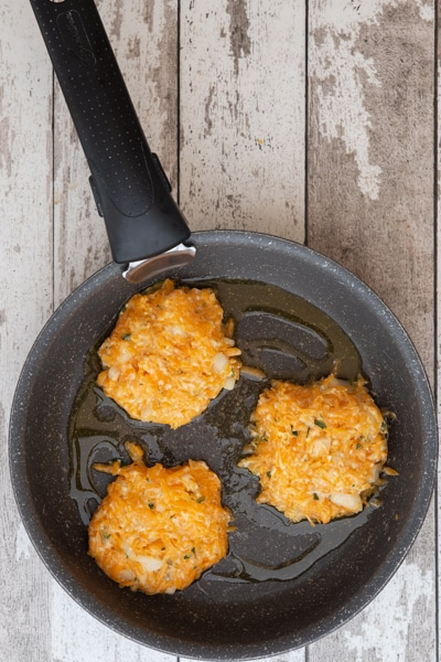 Patties in a frying pan before cooking.