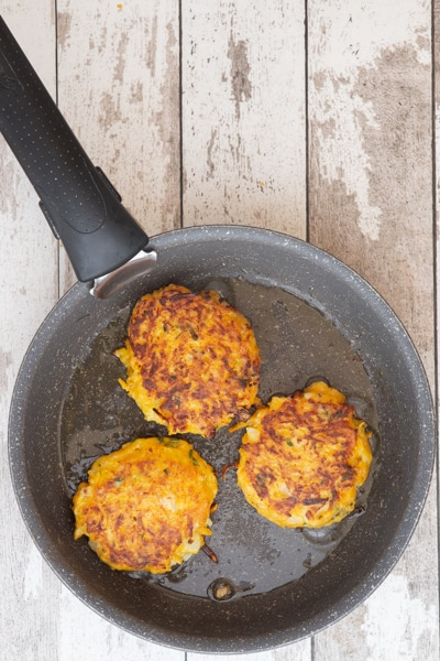 Pumpkin fritter cooked in a frying pan.