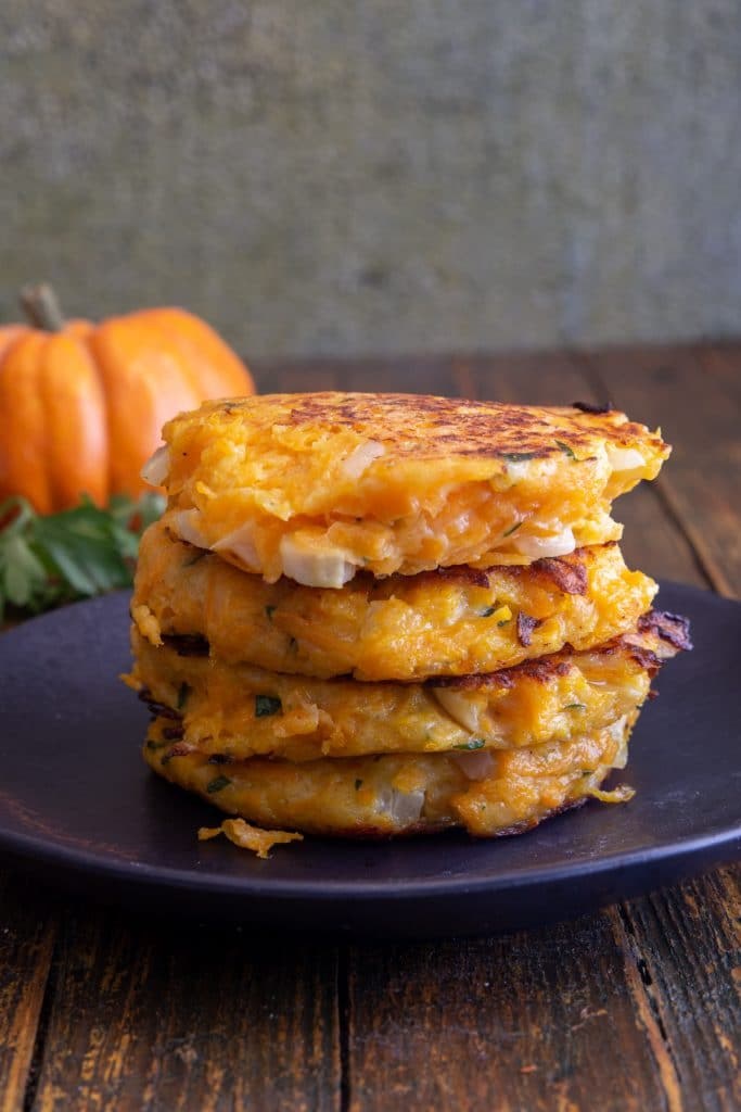 4 Pumpkin fritters stacked on a black plate.