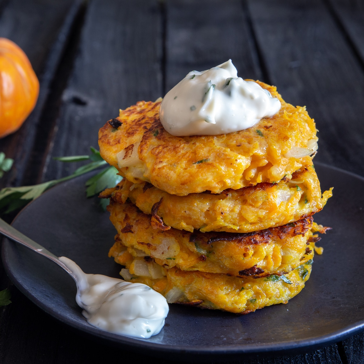 4 Pumpkin fritters stacked with mayo on top.
